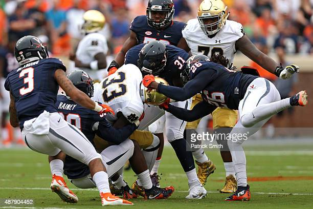 Running back Josh Adams of the Notre Dame Fighting Irish is tackled by cornerback Maurice Canady of the Virginia Cavaliers and teammates in the first...