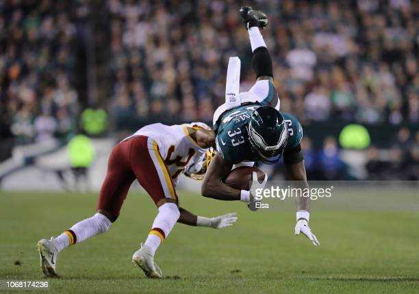 Running back Josh Adams of the Philadelphia Eagles carries the ball as he is tackled by cornerback Greg Stroman of the Washington Redskins in the...