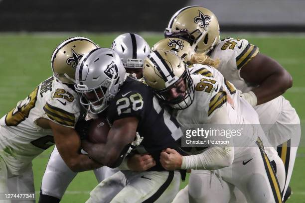Running back Josh Jacobs of the Las Vegas Raiders is tackled by Marshon Lattimore and Trey Hendrickson of the New Orleans Saints as he carries the...
