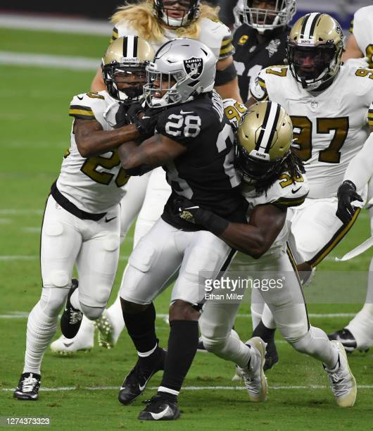 Running back Josh Jacobs of the Las Vegas Raiders is tackled by cornerback Janoris Jenkins and outside linebacker Demario Davis of the New Orleans...