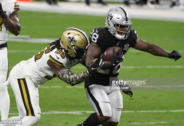 Running back Josh Jacobs of the Las Vegas Raiders is tackled by outside linebacker Demario Davis of the New Orleans Saints during the first half of...