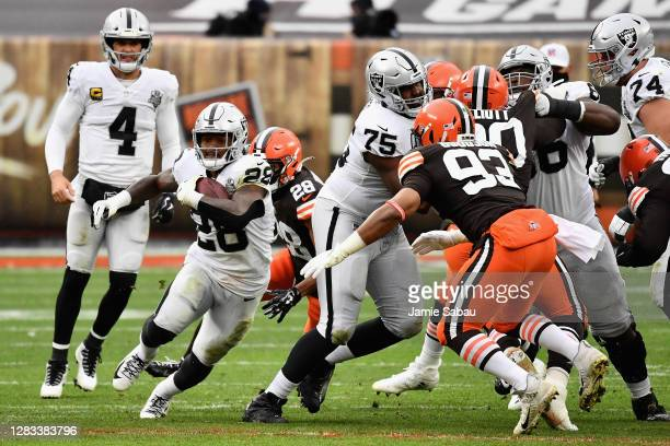 Running back Josh Jacobs of the Las Vegas Raiders rushes the football against middle linebacker B.J. Goodson of the Cleveland Browns during the first...
