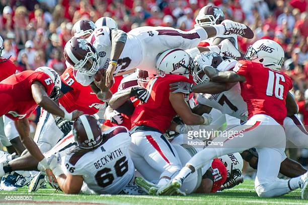 Running back Josh Robinson of the Mississippi State Bulldogs dives over players to score a touchdown during their game against the South Alabama...