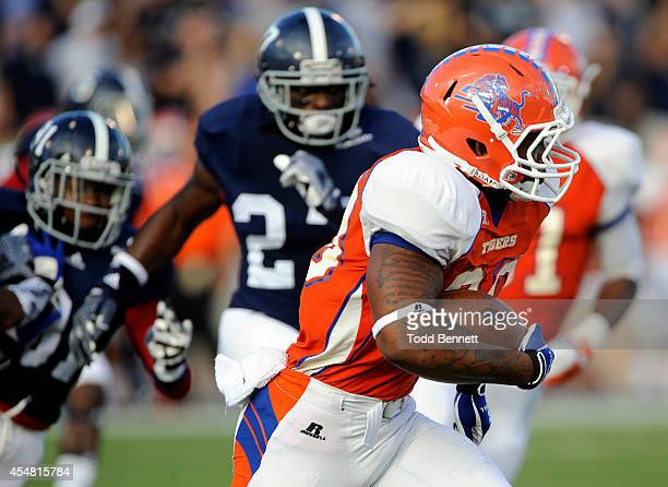 Running back Joshua Berry of the Savannah State Tigers tries to elude Georgia Southern Eagle defenders during the first quarter on September 6 2014...