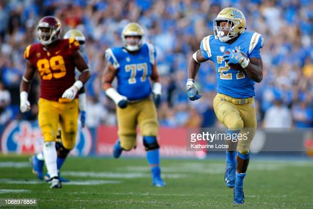 Running back Joshua Kelley of the UCLA Bruins looks over his shoulder as he heads for the end zone during the first second of a football game at Rose...