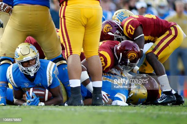 Running back Joshua Kelley of the UCLA Bruins looks up from the bottom of a pile during the second half of a football game at Rose Bowl on November...