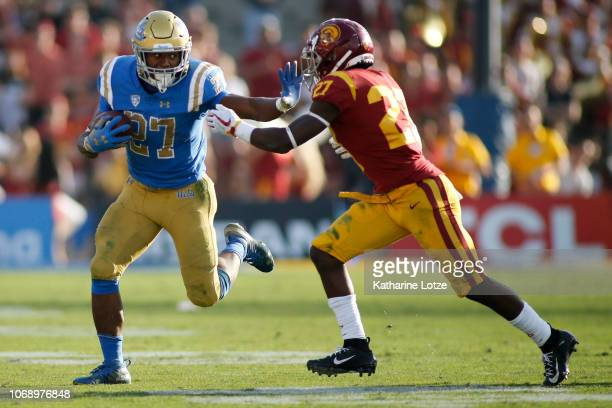 Running back Joshua Kelley of the UCLA Bruins pushes off cornerback Ajene Harris of the USC Trojans during the second half of a football game at Rose...