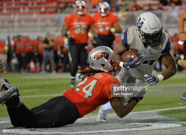 Running back Justen Hervey of the Utah State Aggies is tackled by defensive back Robert Jackson of the UNLV Rebels during their game at Sam Boyd...
