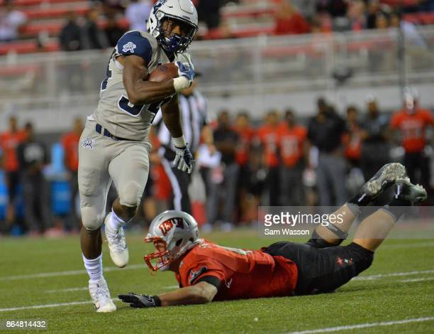 Running back Justen Hervey of the Utah State Aggies runs past linebacker Johnny Stanton of the UNLV Rebels during their game at Sam Boyd Stadium on...