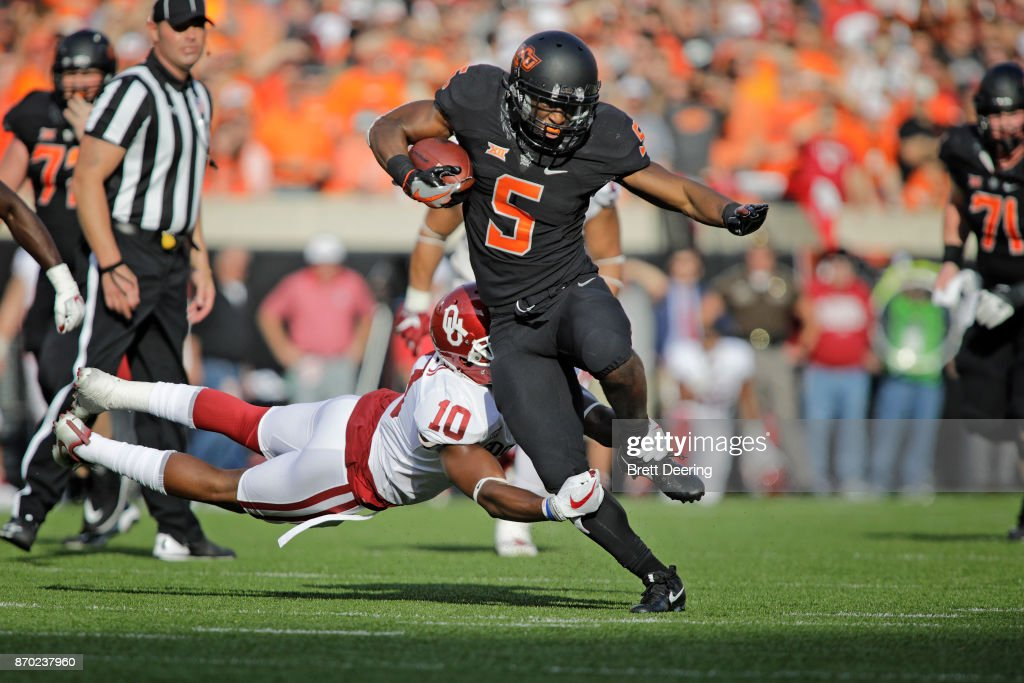 Running back Justice Hill #5 of the Oklahoma State Cowboys is hit by defensive back Steven Parker #10 of the Oklahoma Sooners at Boone Pickens Stadium on November 4, 2017 in Stillwater, Oklahoma.