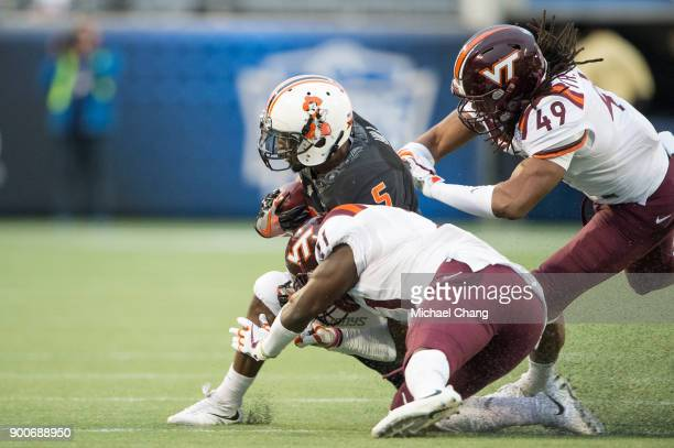Running back Justice Hill of the Oklahoma State Cowboys looks to escape a tackle by safety Reggie Floyd of the Virginia Tech Hokies and linebacker...