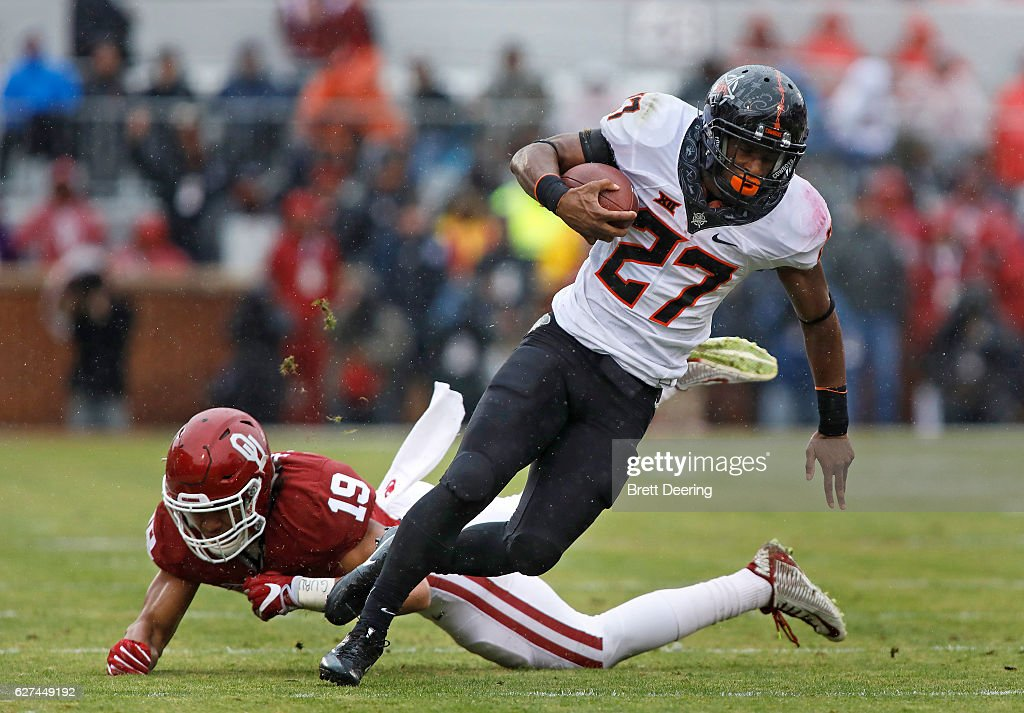 Running back Justice Hill #27 of the Oklahoma State Cowboys makes it past linebacker Caleb Kelly #19 of the Oklahoma Sooners December 3, 2016 at Gaylord Family-Oklahoma Memorial Stadium in Norman, Oklahoma. Oklahoma defeated Oklahoma State 38-20 to become Big XII champions.