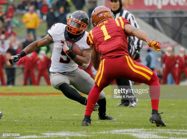 Running back Justice Hill of the Oklahoma State Cowboys rushes for yards past defensive back D'Andre Payne of the Iowa State Cyclones in the first...