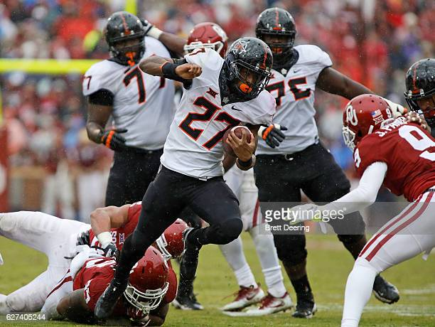 Running back Justice Hill of the Oklahoma State Cowboys tries to get past cornerback Jordan Parker of the Oklahoma Sooners December 3 2016 at Gaylord...