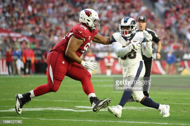 Running back Justin Davis of the Los Angeles Rams rushes the football against defensive tackle Corey Peters of the Arizona Cardinals during the NFL...