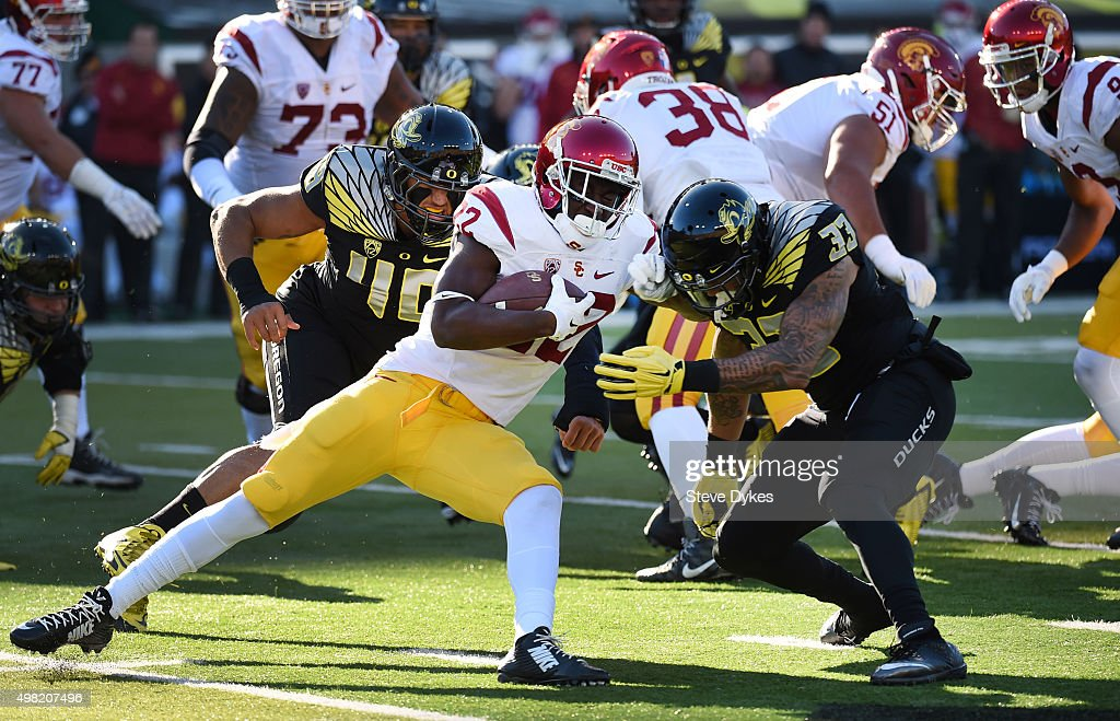 Running back Justin Davis #22 of the USC Trojans is tackled by linebacker Danny Mattingly #46 and linebacker Tyson Coleman #33 of the Oregon Ducks during the first quarter of the game at Autzen Stadium on November 21, 2015 in Eugene, Oregon.