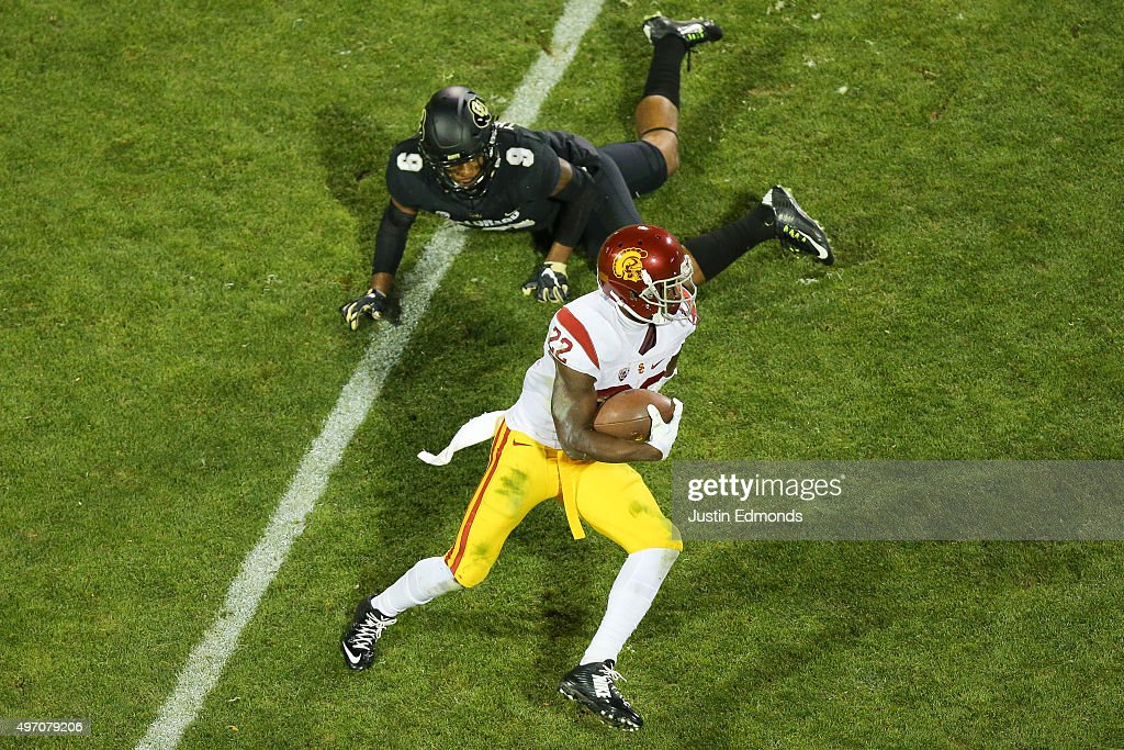 Running back Justin Davis #22 of the USC Trojans runs with the football past defensive back Tedric Thompson #9 of the Colorado Buffaloes during the second quarter at Folsom Field on November 13, 2015 in Boulder, Colorado.