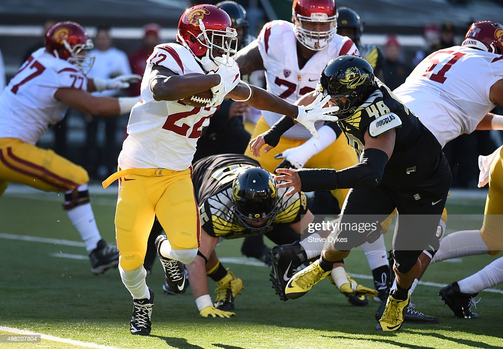 Running back Justin Davis #22 of the USC Trojans tries to avoid the tackle of linebacker Danny Mattingly #46 of the Oregon Ducks during the first quarter of the game at Autzen Stadium on November 21, 2015 in Eugene, Oregon.