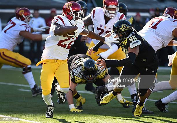 Running back Justin Davis of the USC Trojans tries to avoid the tackle of linebacker Danny Mattingly of the Oregon Ducks during the first quarter of...