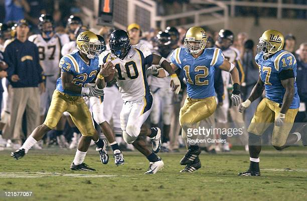 Running back Justin Forett of the Univeristy of California Golden Bears attemptss to run upfield while Bruins linebacker John Hale chases him down in...