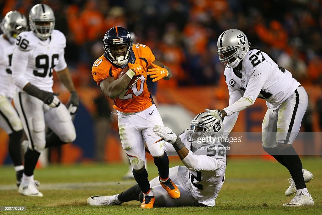 Running back Justin Forsett #20 of the Denver Broncos rushes with the ball as defensive end Khalil Mack #52 of the Oakland Raiders tries to bring him down in the fourth quarter at Sports Authority Field at Mile High on January 1, 2017 in Denver, Colorado.