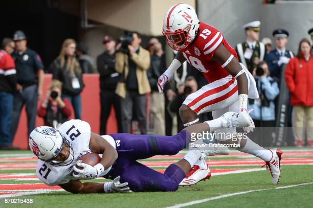 Running back Justin Jackson of the Northwestern Wildcats dives into the end zone ahead of defensive back Marquel Dismuke of the Nebraska Cornhuskers...