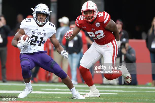 Running back Justin Jackson of the Northwestern Wildcats runs from linebacker Alex Davis of the Nebraska Cornhuskersat Memorial Stadium on November 4...