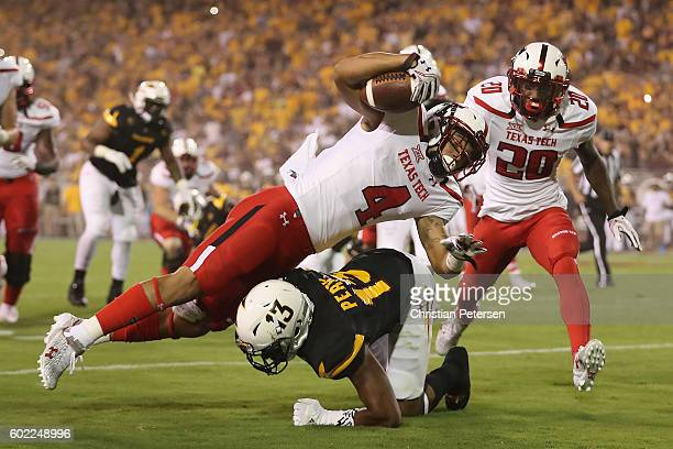 Running back Justin Stockton of the Texas Tech Red Raiders is tackled by defensive back Armand Perry of the Arizona State Sun Devils as he rushes the...