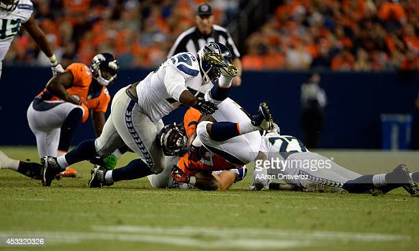 Running back Juwan Thompson of the Denver Broncos gets taken down by linebacker Brock Coyle of the Seattle Seahawks and defensive tackle D'Anthony...
