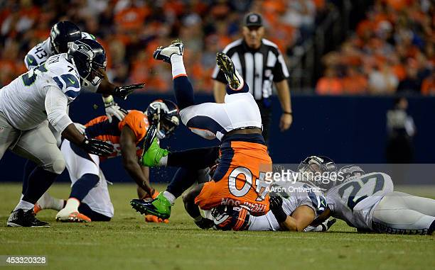 Running back Juwan Thompson of the Denver Broncos gets taken down by linebacker Brock Coyle of the Seattle Seahawks during the first half. The Denver...