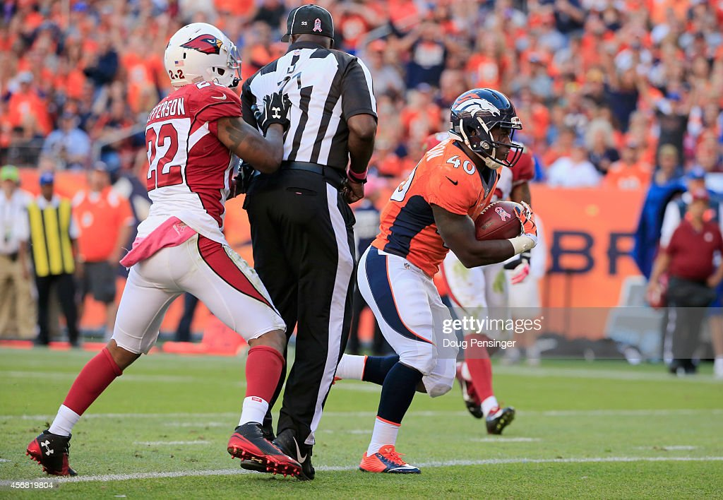 Running back Juwan Thompson #40 of the Denver Broncos rushes 8 yards for a touchdown as strong safety Tony Jefferson #22 of the Arizona Cardinals collieds with umpire Ruben Fowler #71 in the fourth quarter at Sports Authority Field at Mile High on October 5, 2014 in Denver, Colorado. The Broncos defeated the Cardinals 41-20.