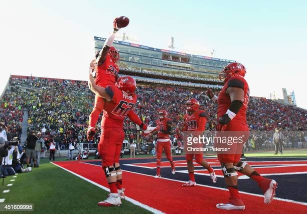 Running back Ka'Deem Carey of the Arizona Wildcats is lifted in the air in celebration by offensive linesman Chris Putton after scoring on a 9 yard...