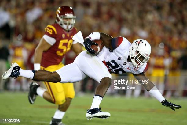 LOS Running back Ka'Deem Carey of the Arizona Wildcats tries to keep his balance as he carries the ball against defensive end JR Tavai of the USC...