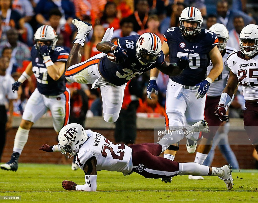 Running back Kamryn Pettway #36 of the Auburn Tigers dives over defensive back Armani Watts #23 of the Texas A&M Aggies as he carries the ball during an NCAA college football game on September 17, 2016 in Auburn, Alabama.