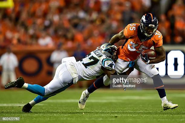 Running back Kapri Bibbs of the Denver Broncos his hit by defensive back Robert McClain of the Carolina Panthers in the third quarter of a game at...