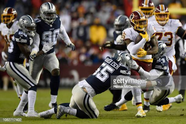 Running back Kapri Bibbs of the Washington Redskins is tackled by linebacker Leighton Vander Esch and defensive end Randy Gregory of the Dallas...