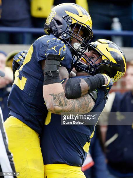 Running back Karan Higdon of the Michigan Wolverines celebrates his 49yard touchdown run against the Rutgers Scarlet Knights with fullback Henry...