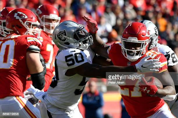 Running back Kareem Hunt of the Kansas City Chiefs carries the ball as linebacker Nicholas Morrow of the Oakland Raiders defends during the game at...