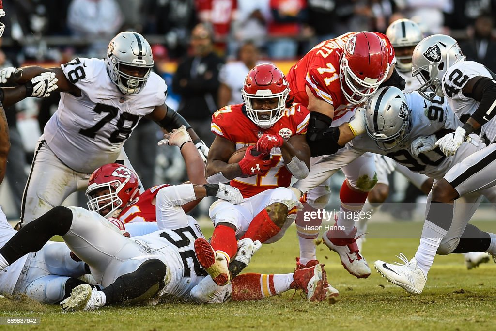 Running back Kareem Hunt #27 of the Kansas City Chiefs falls in to a sea of players after a rush during the fourth quarter against the Oakland Raiders at Arrowhead Stadium on December 10, 2017 in Kansas City, Missouri.