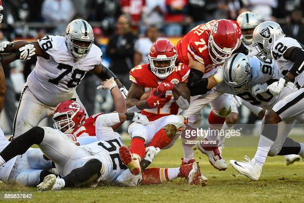 Running back Kareem Hunt of the Kansas City Chiefs falls in to a sea of players after a rush during the fourth quarter against the Oakland Raiders at...