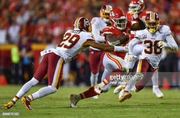Running back Kareem Hunt of the Kansas City Chiefs runs through the tackle attempt of cornerback Kendall Fuller of the Washington Redskins during the...
