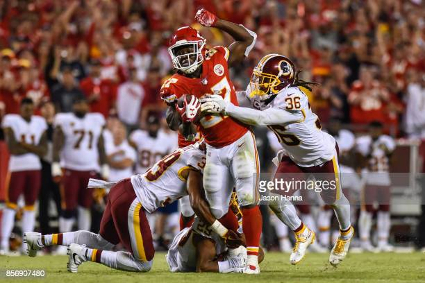 Running back Kareem Hunt of the Kansas City Chiefs runs through the tackle attempt of free safety DJ Swearinger and Keith Marshall of the Washington...