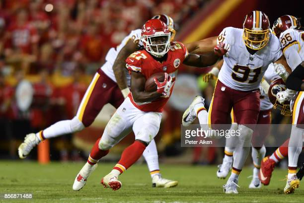 Running back Kareem Hunt of the Kansas City Chiefs rushes the ball in front of outside linebacker Ryan Kerrigan of the Washington Redskins during the...