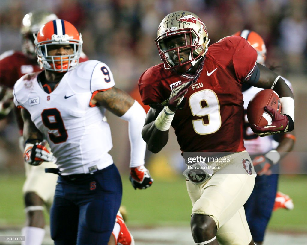 Running back Karlos Williams #9 of the Florida State Seminoles makes a running play during the game against cornerback Ri'Shard Anderson #9 of the Syracuse Orange at Doak Campbell Stadium on Bobby Bowden Field on November 16, 2013 in Tallahassee, Florida. No. 2 Florida State beat Syracuse 59 to 3.