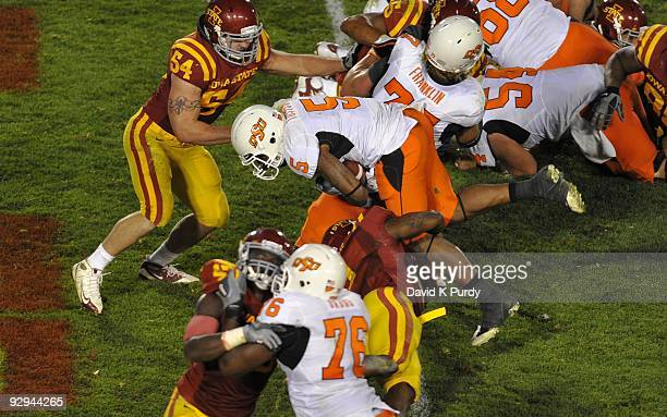 Running back Keith Toston of the Oklahoma State Cowboys jumps up and over Iowa State Cyclones defenders to score a touchdown in the 4th quarter of...