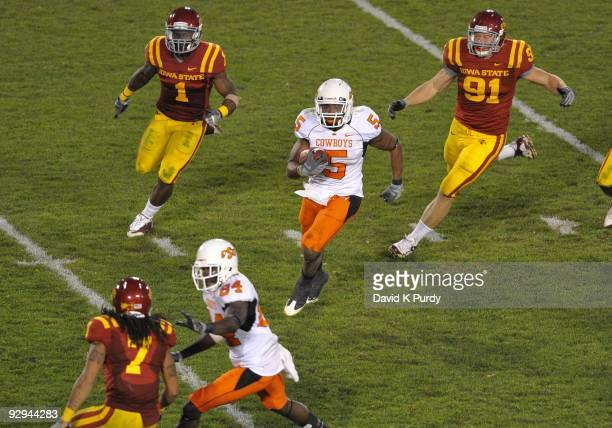 Running back Keith Toston of the Oklahoma State Cowboys rushes for yards against defensive back David Sims and linebacker Patrick Neal of the Iowa...