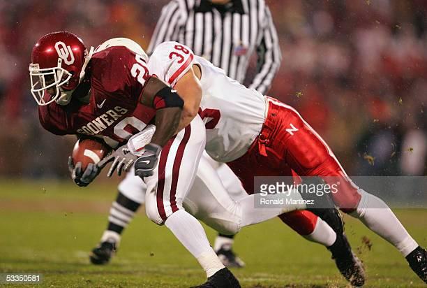 Running back Kejuan Jones of the University of Oklahoma Sooners gets hit by linebacker Barrett Ruud of the University of Nebraska Cornhuskers during...
