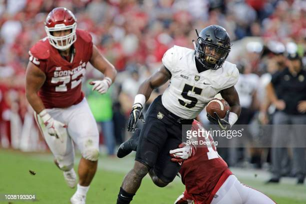 Running back Kell Walker of the Army Black Knights dodges linebacker Curtis Bolton of the Oklahoma Sooners at Gaylord Family Oklahoma Memorial...