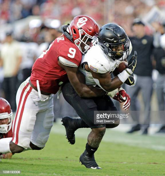 running back Kell Walker of the Army Black Knights is hit by linebacker Kenneth Murray of the Oklahoma Sooners at Gaylord Family Oklahoma Memorial...
