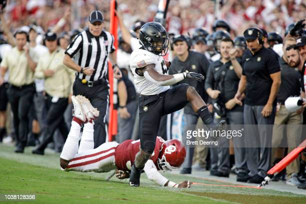 Running back Kell Walker of the Army Black Knights outruns linebacker Ryan Jones of the Oklahoma Sooners at Gaylord Family Oklahoma Memorial Stadium...